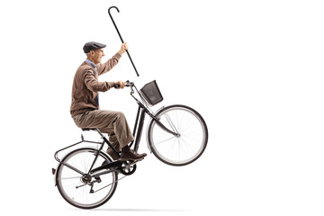 Joyful senior with a cane riding a bicycle and doing a wheelie