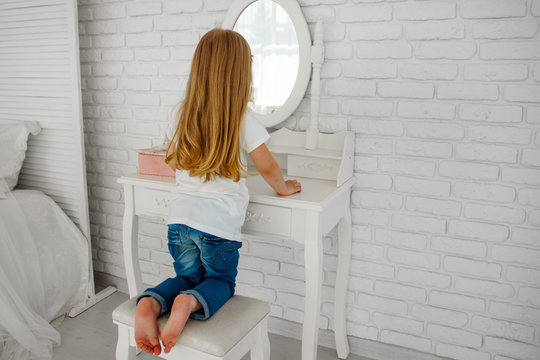 The girl looks in the mirror. Behind the ladies' table. Dressing table.