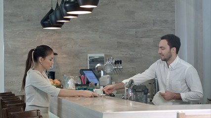 Smiling barista talking to female client finishing her drink