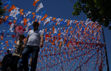 People walk under election posters and party flags in Istanbul