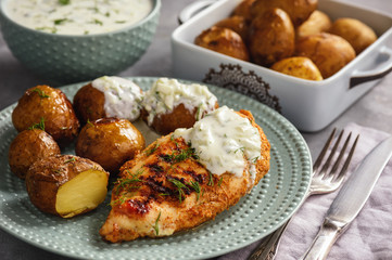 Grilled chicken fillet with baked potatoes and garlic yogurt dip.