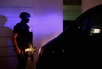 An armed police officer provides security as three men, accused of the assassination of anti-corruption journalist Daphne Caruana Galizia, arrive at the Courts of Justice for the continuation of the compilation of evidence in Valletta