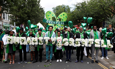 People march during commemorations to mark the first anniversary of the Grenfell Tower fire, near the burn out social housing apartment block in west London