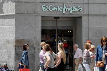 People walk past an El Corte Ingles store in one of the main pedestrian shopping areas, Preciados street, in central Madrid
