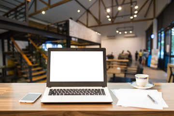 Mockup image of laptop with blank white screen on wooden table of In the coffee shop.