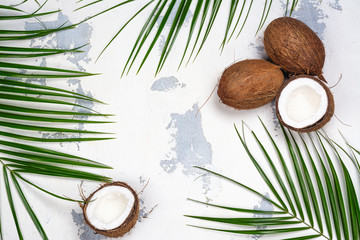 Coconut halves and leaves on white background