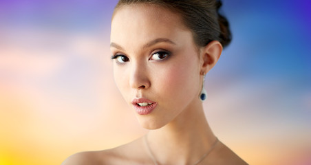 beauty, people, make up and luxury concept - close up of beautiful asian woman or bride with earring over pastel background