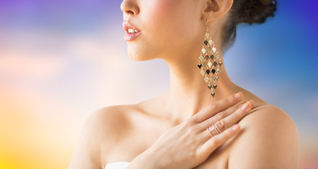 beauty, jewelry and luxury concept - close up of beautiful woman with earrings over pastel background