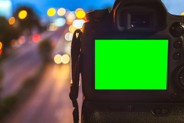 Close-up of DSLR Camera capturing on colorful light abstract circular bokeh background,Night time,Mockup image of with blank screen,DSLR on Tripod,Green screen.