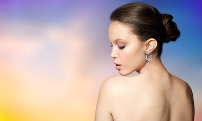 beauty, jewelry, people and luxury concept - close up of beautiful asian woman face with earring over pastel background