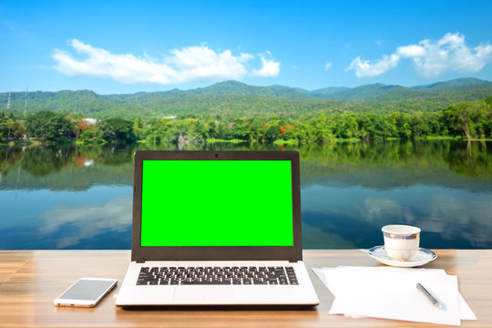 Mockup image of laptop with blank green screen on wooden table of landscape forested Mountain blue sky background.