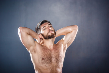 Portrait of shirtless handsome sensual fit young man with naked torso, hands lifted (selective focus)