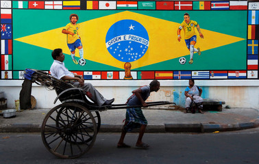 A rickshaw puller transports a passenger past a mural depicting Brazil's Neymar and Marcelo along a street in Kolkata, India