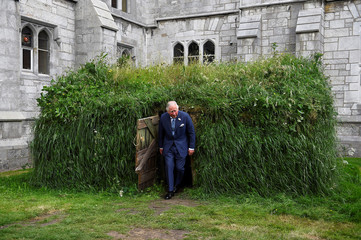 Britain's Prince Charles emerges from a recreation of a potato famine era mud hut on the campus of University College Cork, in Cork