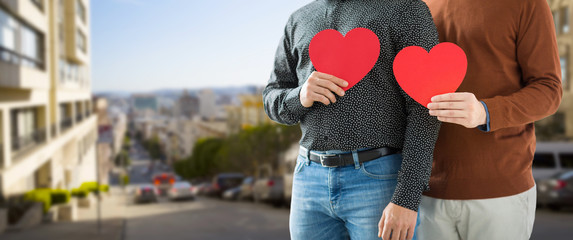 gay pride, lgbt and homosexual concept - close up of happy male couple holding red hearts over san francisco city background