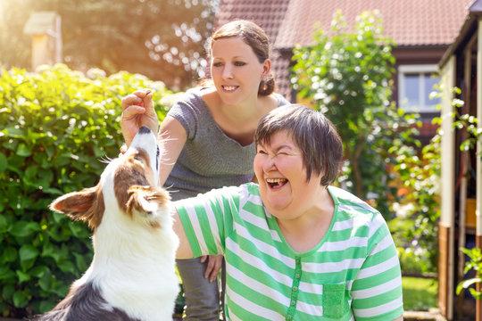 Alternativetherapie mit einem Hund, geistig behinderte Frau und Therapeutin im Garten