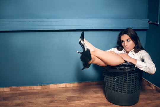 Gorgeous woman in trash can. Beautiful bored office lady got herself stuck in black trash can with her legs out. Dark blue wall in background.