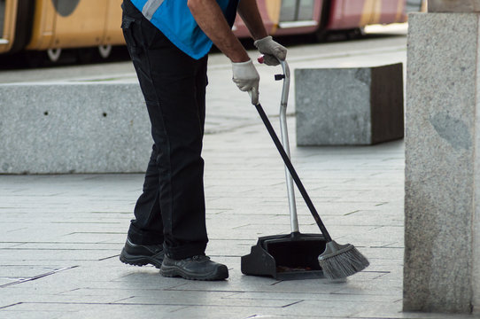 closeup of man cleaning the front of train station with broom