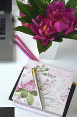 Bold pink peonies on white and black theme creative workspace with stationery closeup.  Freelancing and working from home. Feminine lifestyle and creative work desktop.