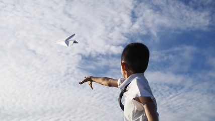 Asian school boy playing with paper airplane.(Selected focus)