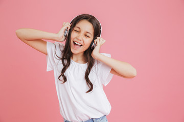 Happy teen girl 8-10 in casual clothing singing with closed eyes while listening to music via wireless headphones, isolated over pink background Fotobehang