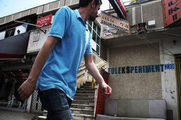 "A man passes by graffitti saying ""EULEKSPERIMENT"" in Pristina"