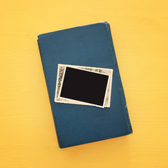 top view of blank photo frames over old book on yellow wooden background.