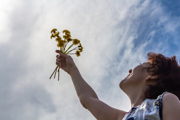 A woman in a cotton dress holds dandelions and laughs