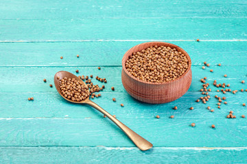 coriander, seeds in a wooden bowl, spoon, blue background, spice