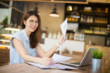 Beautiful young Asia woman working with laptop a at cafe