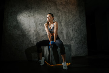 young beautiful girl boxer in a dark gym