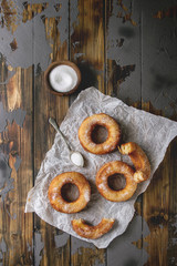 Homemade puff pastry deep fried donuts or cronuts in stack with sugar standing on crumpled paper over dark wooden concrete texture background. Flat lay, space.