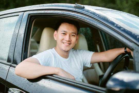 Close up of a handsome Asia man siting in his car.Travel concept..