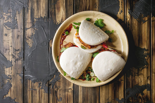 Asian sandwich steamed gua bao buns with pork belly, greens and vegetables served in ceramic plate over dark wooden plank background. Asian style fast food dinner. Flat lay, space