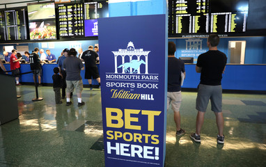 Gamblers place bets on sports at Monmouth Park Sports Book by William Hill, shortly after the opening of the first day of legal betting on sports in Oceanport