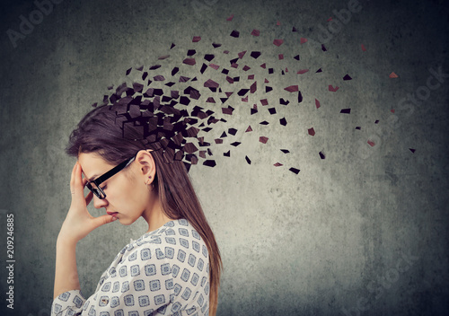 Wall mural Young woman losing parts of head as symbol of decreased mind function.