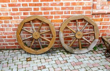 Old wooden wagon wheels near the brick wall