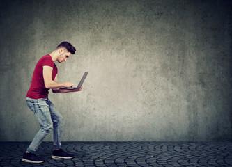 Man surfing modern laptop on gray wall