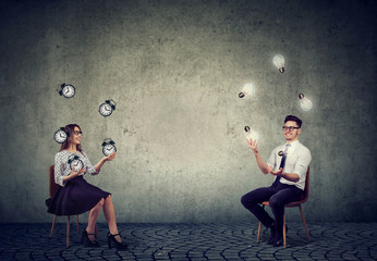 Business man juggling with idea light bulbs with business woman managing time and efficiency