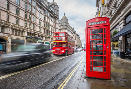 London, England - Iconic blurred black londoner taxi and vintage red double-decker bus on the move with traditional red telephone box in the center of London at daytime