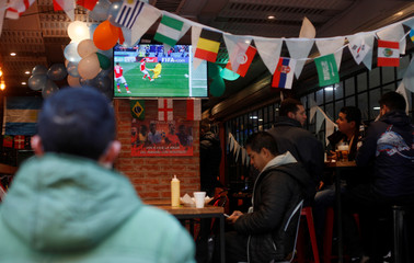People watch the World Cup Group A Russia vs Saudi Arabia soccer match at a bar in Buenos Aires