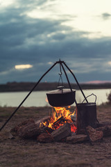Preparing food on campfire in wild camping, resting on the nature