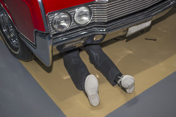 a man lying on the ground under the car, performs repair work. feet under the car. Carrying out a self-inspection
