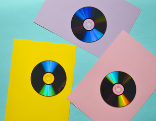 Computer CDs on a colored paper background. Retro Media. Top view.