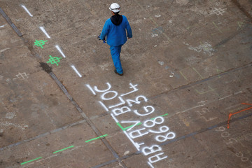A shipbulding worker walks in the STX France shipyard site in Saint-Nazaire