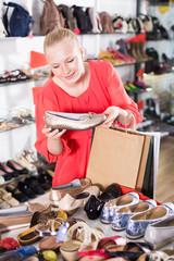 Adult girl is choosing ballet shoes