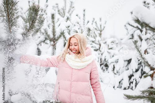 b668e0061 Young blond woman in a pink down jacket winter portrait with snow ...