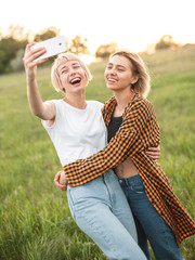 Two young women shoot photos of themselfs on mobile phone. Best friends