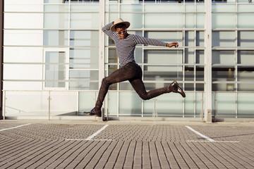 Stylish black man jumping on street