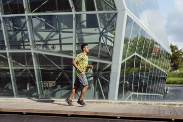 Handsome ethnic man jogging in city